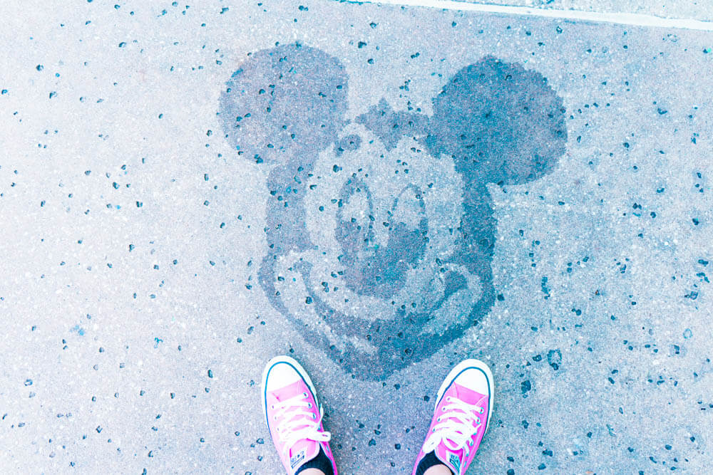 Hidden Mickey on sidewalk of All Star Resort with pink converse shoes