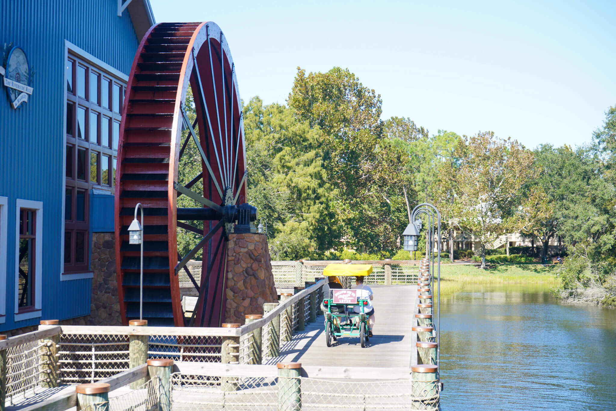 Port Orleans Riverside bridge and watermill wheel with a surrey bike