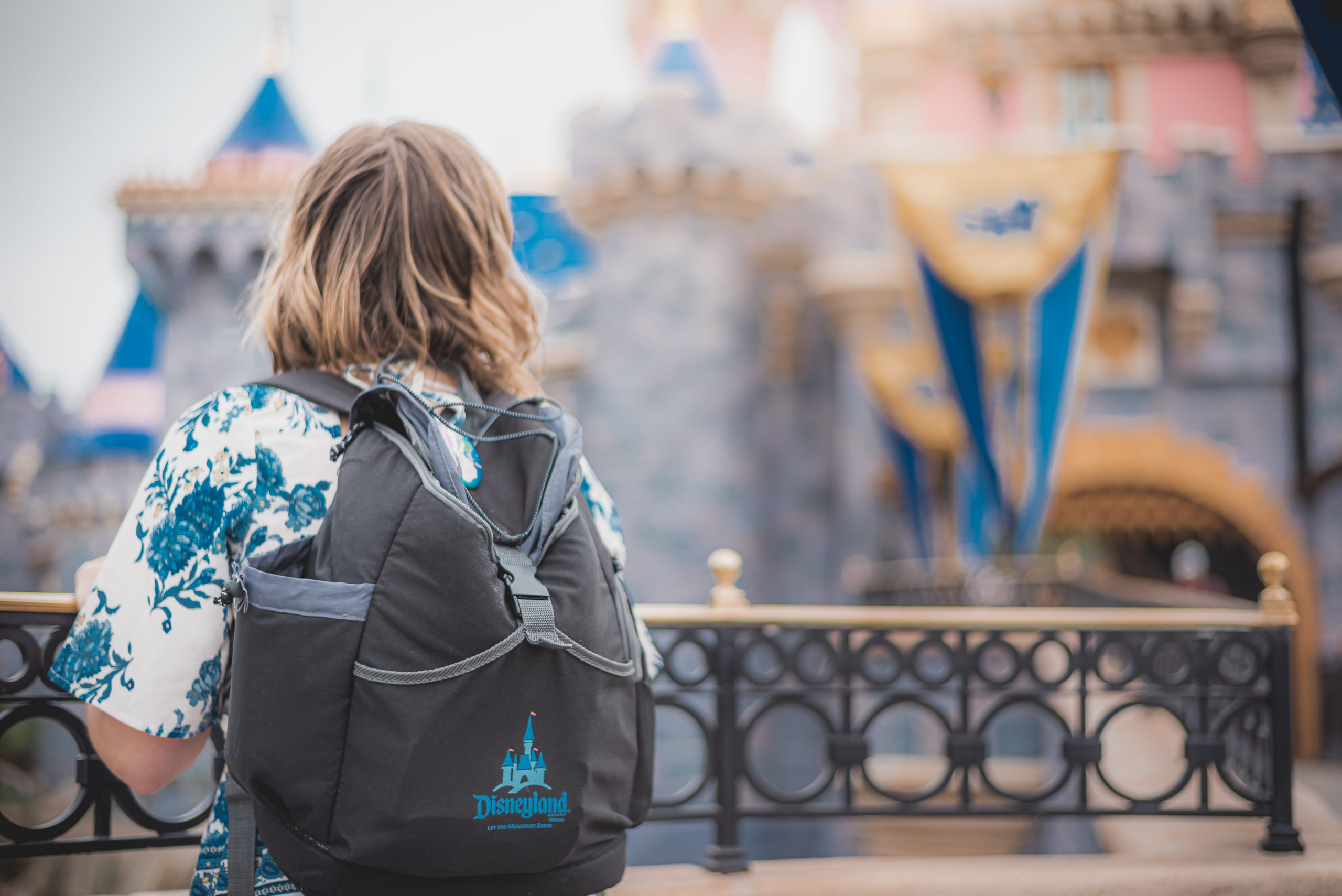 Woman with Disneyland Backpack facing Sleeping Beauty Castle